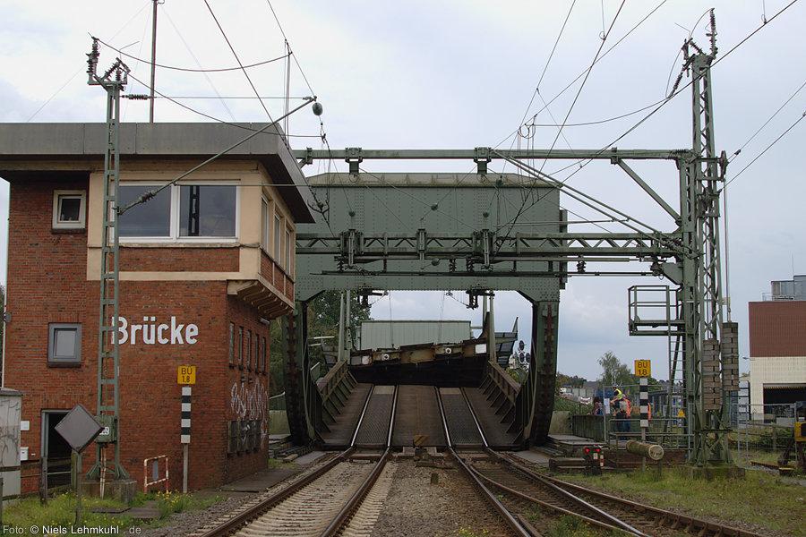Blick vom Bahnübergang Am Stau auf die sich öffnende Rollklappbrücke
